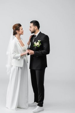Smiling bride in wedding suit hugging arabian groom on white background stock vector