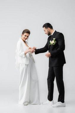 Cheerful bride wearing handcuffs on muslim boyfriend on white background stock vector