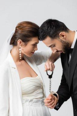 Bride holding handcuffs near upset muslim groom isolated on grey stock vector