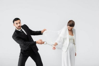 Muslim groom pulling handcuffs and veil of sad bride isolated on grey stock vector