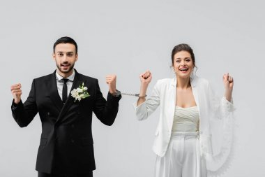 Cheerful interracial couple of newlyweds in handcuffs showing yeah gesture isolated on grey stock vector