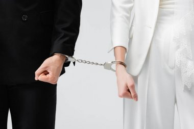 Cropped view of bride and groom in handcuffs isolated on grey stock vector
