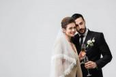 Lächelnde Braut in Schleier hält Glas Champagner neben arabischem Freund