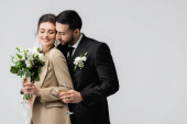 eleganter arabischer Mann mit Champagnerglas umarmt glückliche Braut hält Brautstrauß isoliert auf grau