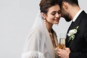 šťastná nevěsta s arabským snoubencem drží sklenice šampaňského izolované na šedé