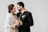 glückliche Braut mit Champagnerglas umarmt Hals von eleganten arabischen Mann isoliert auf grau