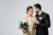 elegáns arab vőlegény kéz a kézben boldog fiatal menyasszony elszigetelt szürke