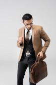 mladý arabský muž v módním obleku chůze s koženou taškou izolované na šedé