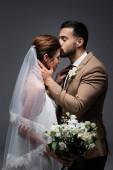muslim muž líbání nevěsta drží svatební kytice izolované na šedé