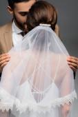 arabský muž objímající ramena nevěsty v závoji izolovaném na šedi