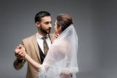 šťastný, mezirasový novomanželský pár tanec izolovaný na šedi