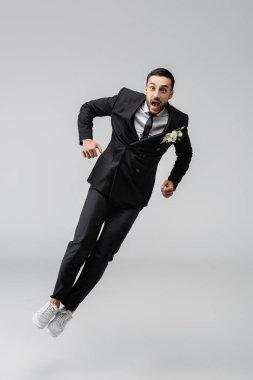 Amazed arabian groom jumping isolated on grey stock vector