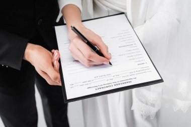 Cropped view of couple signing marriage contract isolated on grey stock vector