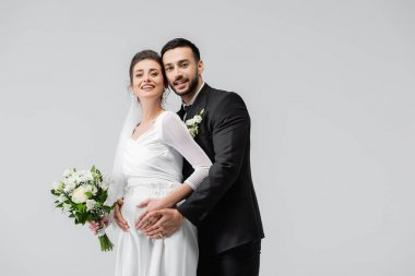 Young muslim groom embracing cheerful pregnant bride with wedding bouquet isolated on grey stock vector