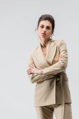 Gri renkte poz verirken kameraya bakan modacı kadın