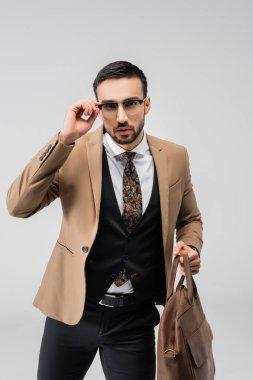 Elegant muslim man adjusting eyeglasses while holding leather bag isolated on grey stock vector