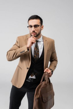 Fashionable muslim man holding leather bag and touching chin isolated on grey stock vector