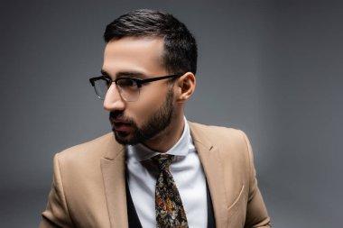Brunette muslim man in eyeglasses looking away on grey stock vector