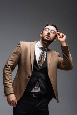 Fashionable arabian man adjusting eyeglasses while looking up on grey stock vector
