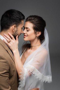 Joyful woman in veil touching face of muslim bridegroom isolated on grey stock vector