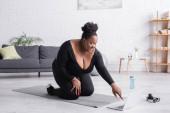 šťastný africký Američan plus velikost žena sledování sportovní trénink na notebooku, zatímco sedí na fitness podložka v obývacím pokoji