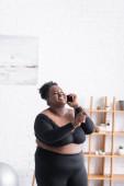 šťastný africký Američan plus velikost žena ve sportovním oblečení mluví na smartphone a ukazuje prstem