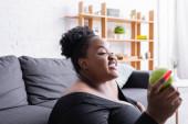 lächelnde afrikanisch-amerikanische Plus-Size-Frau in Sportbekleidung mit grünem Apfel