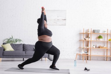 Full length of cheerful african american plus size woman in sportswear standing in yoga pose in living room stock vector