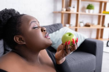 African american plus size woman with closed eyes holding green apple stock vector