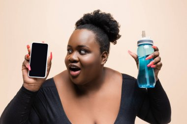 Amazed african american plus size woman holding sports bottle and smartphone with blank screen isolated on beige stock vector