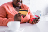 cropped view of happy african american plus size woman holding credit card and smartphone