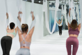 back view of young sportswomen warming up with fly yoga hammocks on blurred foreground