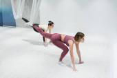 mladé sportovkyženy protahování nohy s muškou jóga popruhy v tělocvičně