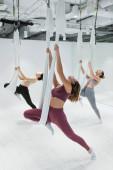 sportos fiatal nők nyújtózkodnak légi jóga függőágyon fitneszközpontban