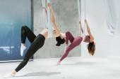 junge sportliche Frauen beim Training mit Fliege-Yoga-Hängematten im Sportzentrum