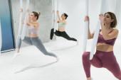 drei junge Sportlerinnen praktizieren Aerial Yoga auf verschwommenem Vordergrund