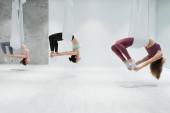 boční pohled na tři mladé ženy cvičící leteckou jógu v tělocvičně