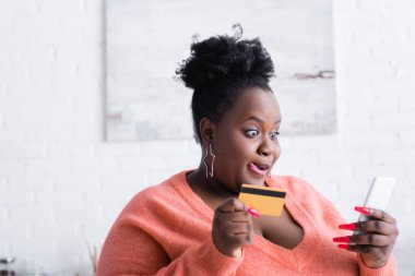 African american plus size woman sticking out tongue while holding credit card and smartphone stock vector