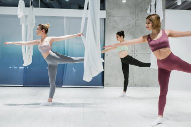 three young women practicing warrior pose near fly yoga hammocks in sports center