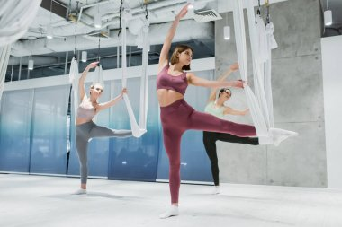 group of young women stretching legs with aerial yoga straps