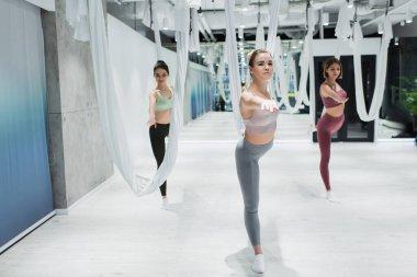 sportive women practicing warrior pose near fly yoga hammocks in gym