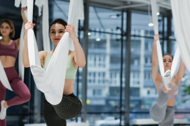 happy woman stretching on fly yoga hammock near group on blurred background