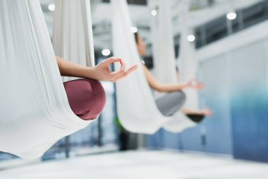 sportswomen meditating in lotus pose while practicing fly yoga, blurred background