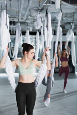 young woman exercising with aerial yoga hammock near group on blurred background