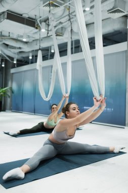 young sportswomen sitting on fitness mats and stretching with aerial yoga hammocks