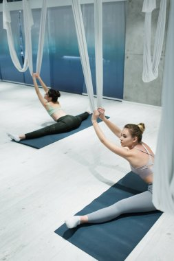 high angle view of women stretching with aerial yoga straps while sitting on fitness mats