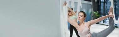 Young woman warming up with fly yoga straps in sports center, banner