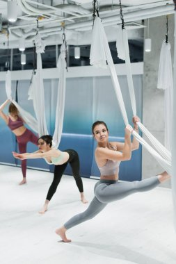 Barefoot sportswoman working out with fly yoga hammock near women on blurred background in fitness center
