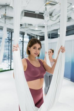 Sportswoman in sportswear looking at camera during fly yoga exercise