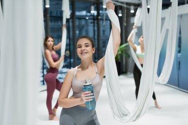 Cheerful woman holding sports bottle near fly yoga hammocks and sportswomen on blurred background